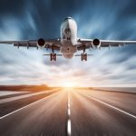 Airplane and road with motion blur effect at sunset. Landscape with passenger airplane is flying over the asphalt road and cloudy sky. Commercial plane is landing. Aircraft with blurred background